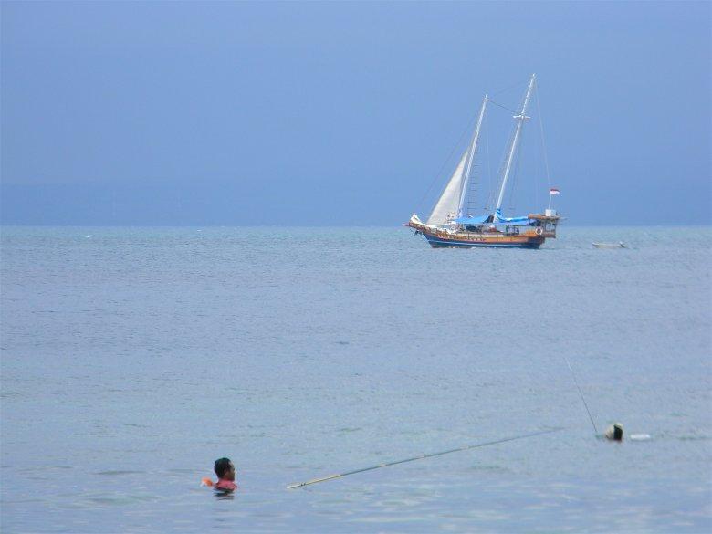 Wędkarz łowi ryby stojąc bezpośrednio na rafie koralowej - Gili Air.