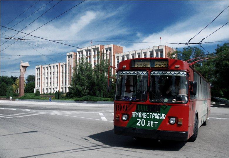 """Tyraspol, stolica republiki – trolejbus pomalowany w barwy państwowe orz napis """"Naddniestrze ma 20 lat"""" zawraca na placu przed pałacem prezydenckim. W tle widoczny pomnik Lenina"""