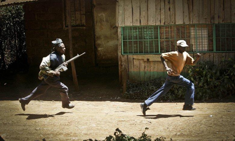Kenijski policjant biegnie za demonstrantem w miejscowości Nderi.