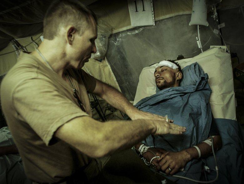 Amerykański lekarz bada więźnia rannego w moździerzowym ataku na wiezienie Abu Ghraib.