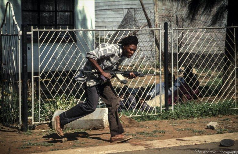 Bojownik ANC biegnie z kałasznikowem podczas walk z członkami IFP w Takozie.