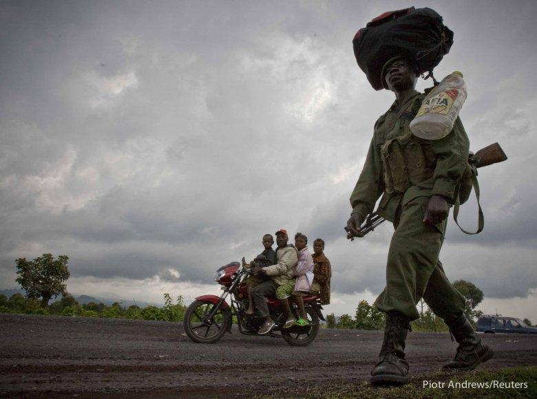 Rodzina w podróży i kongijski żołnierz, na drodze we wschodnim Kongo.