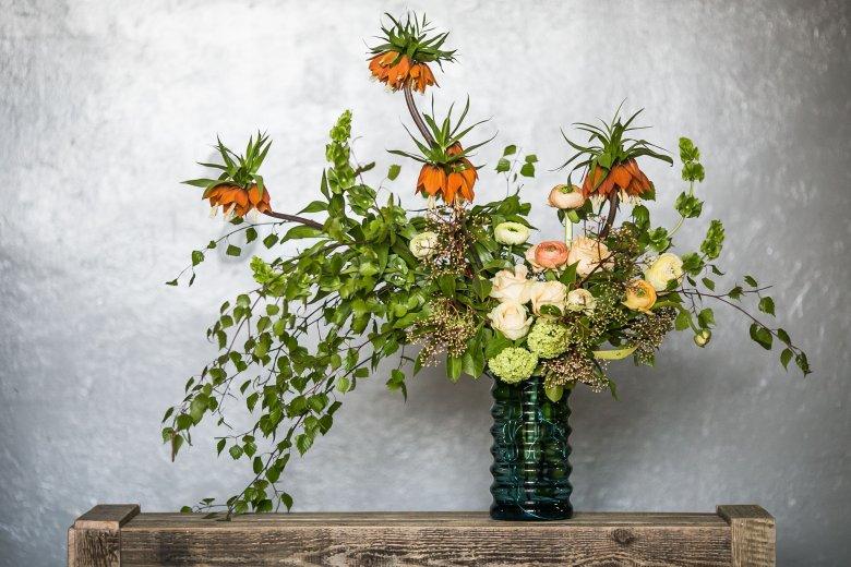 Przepiękna pomarańczowa szachownica cesarska, molucella, pełnik i róża w towarzystwie delikatnych gałązek brzozowych i czeremchy. Przepiękna kompozycja.