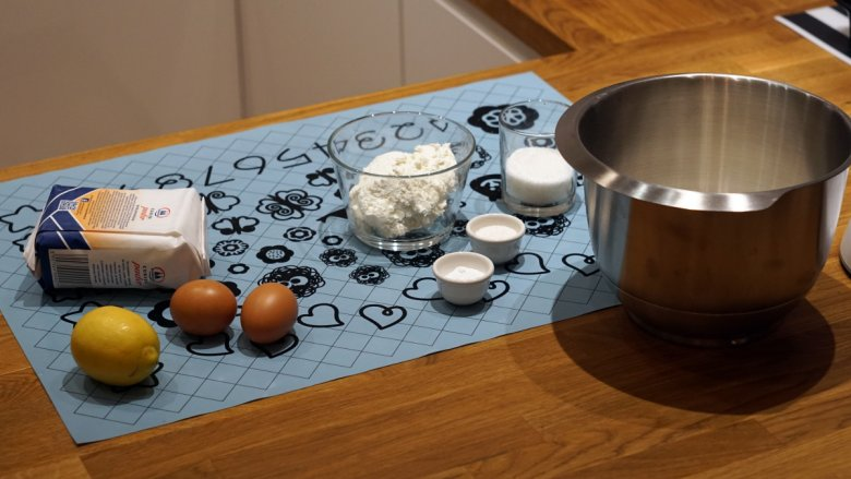 Składniki na oponki serowe i lukier. W metalowej misce jużjest mąka.