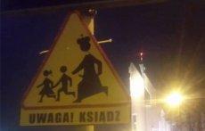Toruń: Ksiądz biegnący za dziećmi na znaku drogowym obok kościoła.