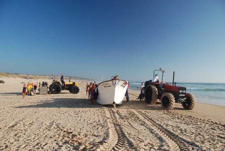 Łódź już po powrocie na ląd i traktory wyciągające sieć z wody.