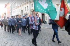 Przed oficjelami defilowało dwóch młodzieńców z flagami ONR.