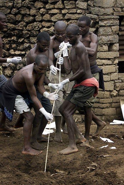 Więźniowie pracujący przy ekshumacji ciał zamordowanych członków sekty.