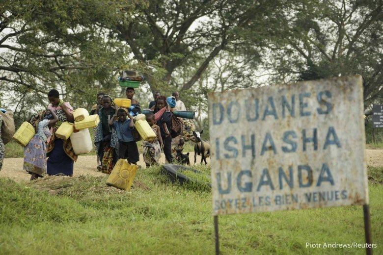 Uchodźcy przekraczający granicę Ugandy.