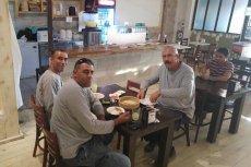 Arabowie i Żyd jedzą humus w izraelskiej kawiarni.