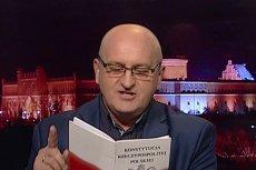 Marian Kowalski w robi zagorzałego czytelnika Konstytucji RP.