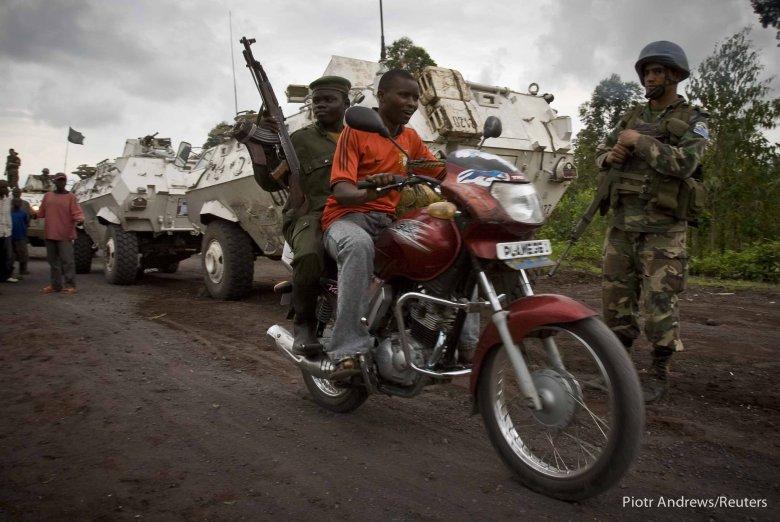 Mężczyzna podwozi kongijskiego żołnierza na linię frontu.
