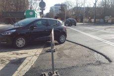 Drogowcy nowy asfalt kładli dookoła źle zaparkowanych samochodów.