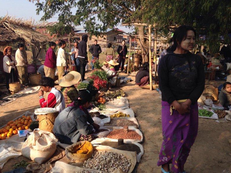 Targ w Ywama. Na pierwszym planie kobieta z charakterystycznie dla Birmanek umalowaną twarzą. Nakładają one substancję o nazwie thanaka, mieszaninę sproszkowanego drewna z wodą, która chroni twarz przed słońcem, ale ma również  zdobić.