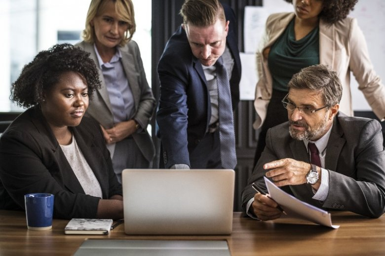 To jedno z wielu biurowych zdjęć ze stocka przedstawiających zespół pracowników przy jednym komputerze. Fotografie tego typu zainspirowały twórców projektu