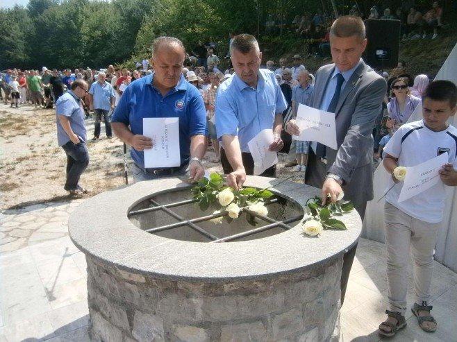 Jasmin Mešković i inni uczestnicy obchodów składją kwiaty na wejściu do jaskini.