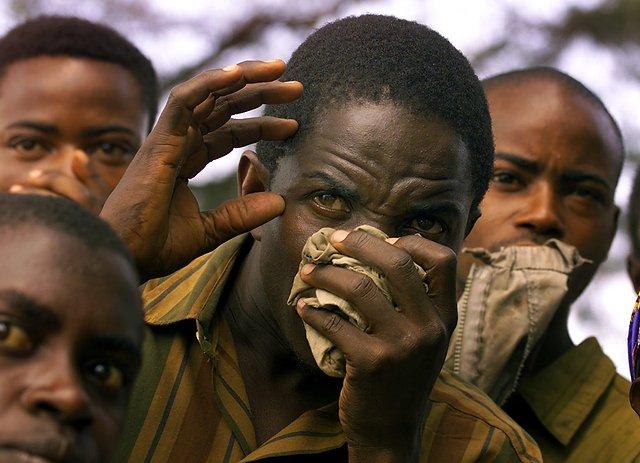 Mieszkańcy wioski Rugazi przypatrują się z przerażeniem ekshumacji ciał zamordowanych członków sekty.