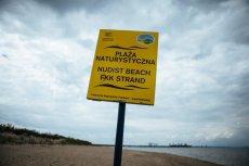 Nudyści, nieświadomi granic plaży dla naturystów, opalają się w strefie dla okrytych plażowiczów.