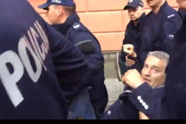 Policjanci siłą usuwają Frasyniuka, by oczyścić Krakowskie Przedmieście na wiec PiS.