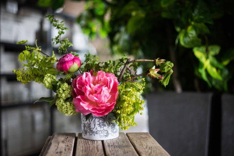 Bezpretensjonalny, romantyczny bukiet z peonii, liści orzecha, gałązek kasztanowca, klonu i głogu ustawiony w starej cukiernicy.