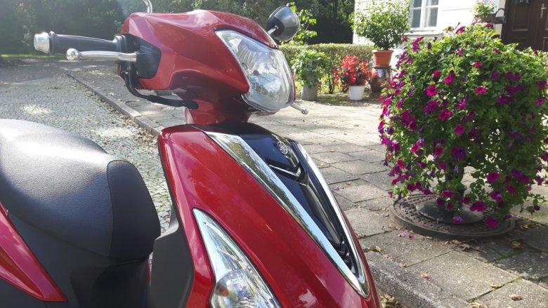 Czerwona Yamaha jest to mały, elegancki skuter.