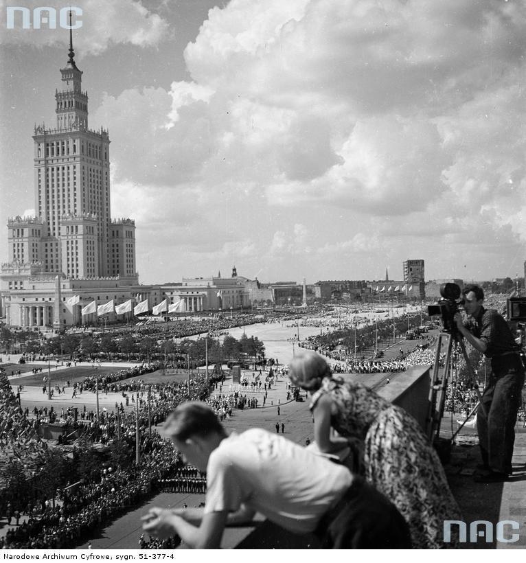 Pałac Kultury i Nauki oraz plac Defilad widoczne z dachu budynku przy ulicy Marszałkowskiej. Z prawej operator kamery filmuje pochód (1955).