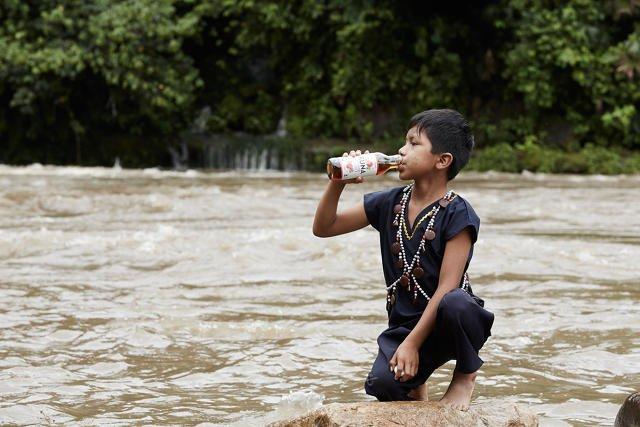 Indiańskie dziecko z butelką napoju Runa