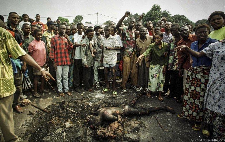 Tłum pokazuje spalone ciało mężczyzny z plemienia Tutsi