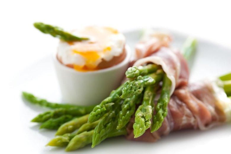 Szparag na śniadanie? Czemu nie! Na przykład w towarzystwie jajka na miękko i owinięty w plasterek szynki parmeńskiej.