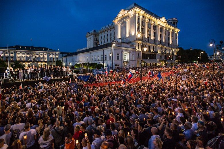 """Flagi, świece, znicze i konstytucje - to """"broń"""" manifestantów spod Pałacu Prezydenckiego."""