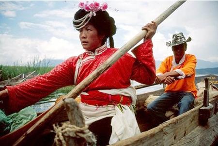 Kobieta w tradycyjnym stroju Mosuo i mężczyzna na canoe.