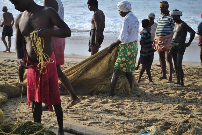 Dzieci kręcą się w pobliżu rybaków z Kerali zarówno przed wypłynięciem w morze, jak i po powrocie. Czasem tylko przeszkadzają przy składaniu sieci. Morze Arabskie, Kovalam, Indie.