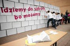 Dzieci z autyzmem burzą symboliczny mur, który utrudnia im pójście do szkoły. Ten happening zorganizowano w 2013 r. w Łodzi.