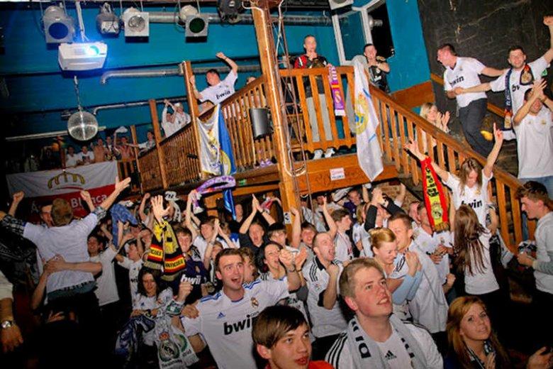 Kibice z fanklubu Realu Madryt wspólnie oglądają mecz.