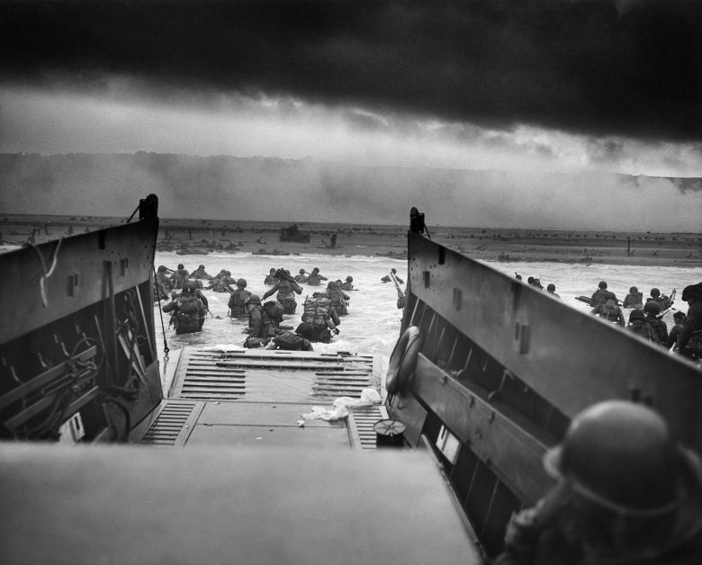 """Into the Jaws of Death — U.S. Troops wading through water and Nazi gunfire"""