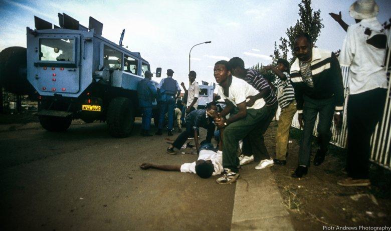Członkowie ANC próbują odciągnąć kolegę zabitego chwilę wcześniej w trakcie  strzelaniny w Takozie.