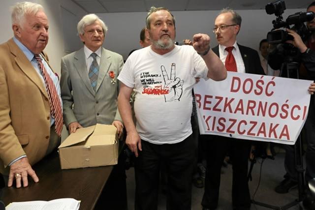 """Tortem rzucił w sędzię Zygmunt Miernik ( w koszulce z napisem """"Solidarność""""). Z prawej strony widoczny jest trzymający transparent Adam Słomka"""