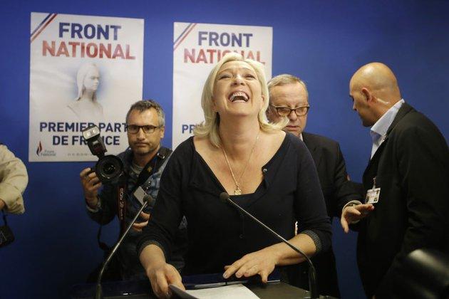 """Marine Le Pen na tle plakatów """"Front Narodowy - pierwszą partią Francji"""""""