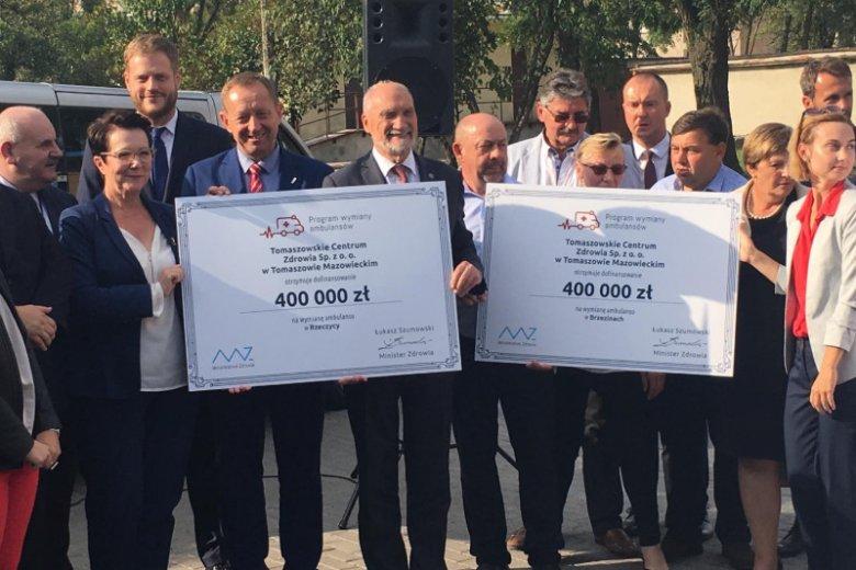 Antoni Macierewicz trzyma czek, a wiceminister zdrowia stoi w drugim rzędzie.