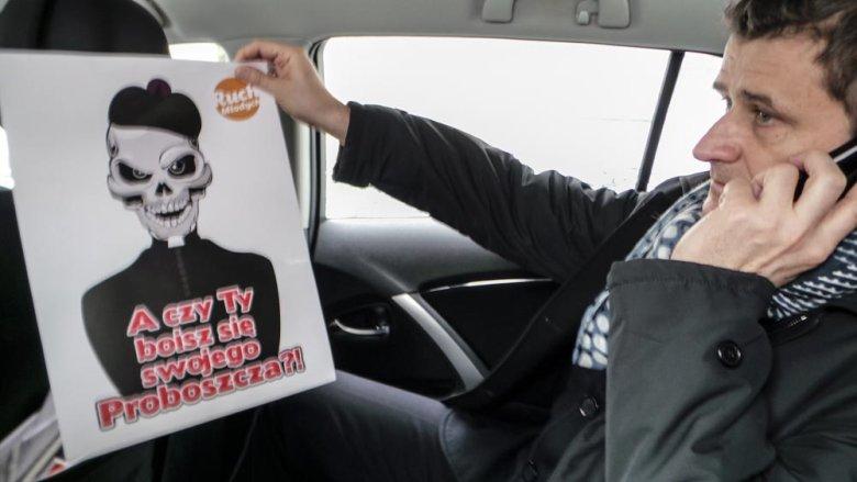 Janusz Palikot w samochodzie. W drodze na kolejne spotkanie dostaje z biura informacje, jak poszło mu w mediach