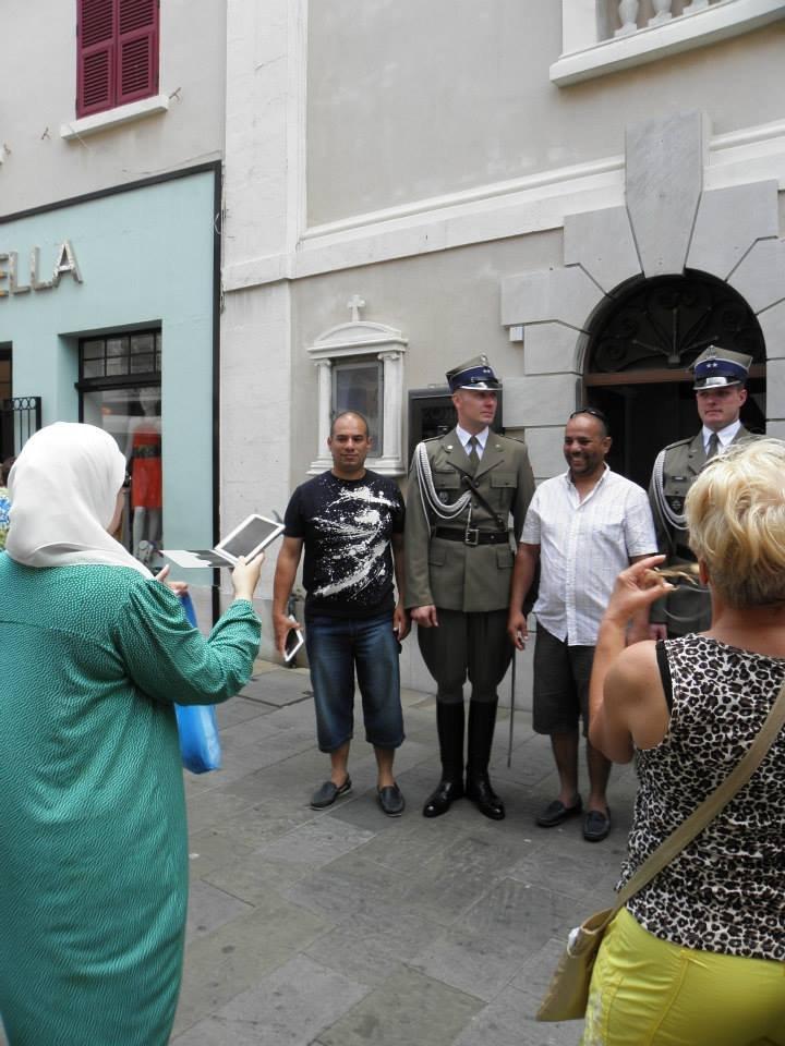 Muzułmanie robiący sobie zdjęcia z polskimi żołnierzami wychodzącymi z Katedry przy Main Street.