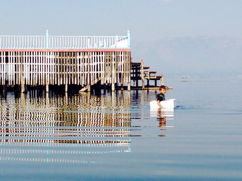 Mały chłopiec pływający  wokół starego domu w styropianowym  pudle. Inleh Bo The/Jezioro Inle/Birma
