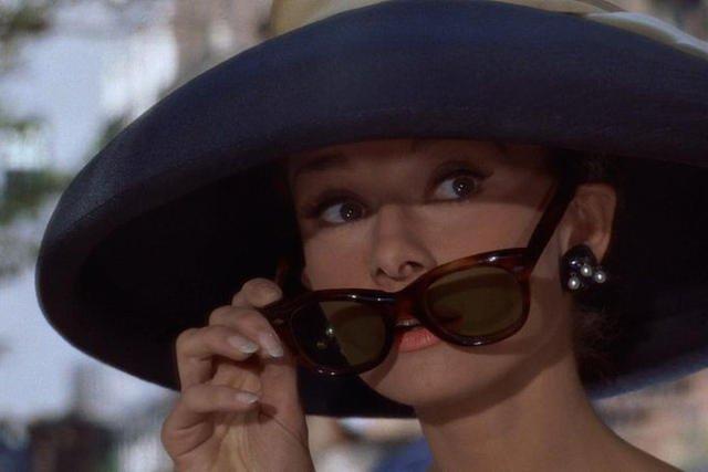 """Audrey Hepburn w filmie """"Śniadanie u Tiffany'ego"""" i jeden z jej znaków rozpoznawczych - kocie okulary przeciwsłoneczne."""