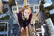 Angela  Nikolau robi selfie znad krawędzi drapaczy chmur.