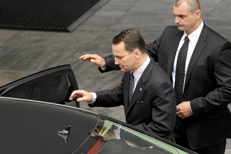 Radosław Sikorski wsiadający do służbowego samochodu.