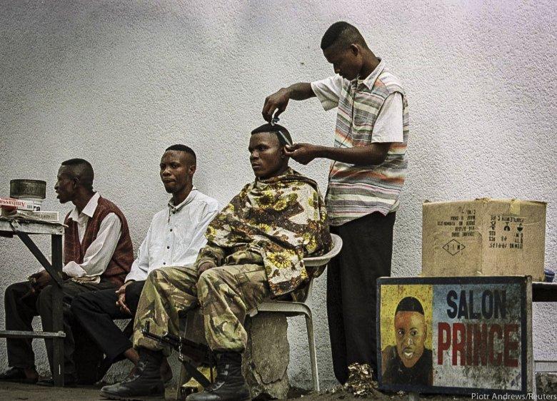 Miejscowy fryzjer strzyże żołnierza lojalnego Kabili