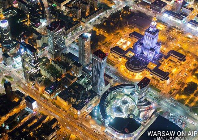 """Kolekcja fotografii """"WARSAW ON AIR by Maciej Margas"""" powstała z pokładu śmigłowca, gdzie 22-letni fotograf przy otwartych drzwiach przyczepiony linami wykonał jako pierwszy w Polsce dzienne i nocne panoramy Warszawy."""