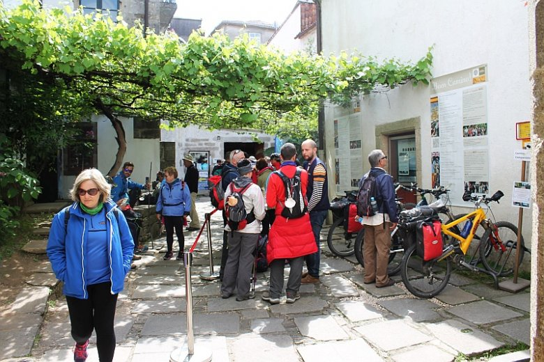 Pielgrzymi czekający w kolejce do Oficina de Peregrinaciones, by potwierdzić swój udział w Camino de Santiago.