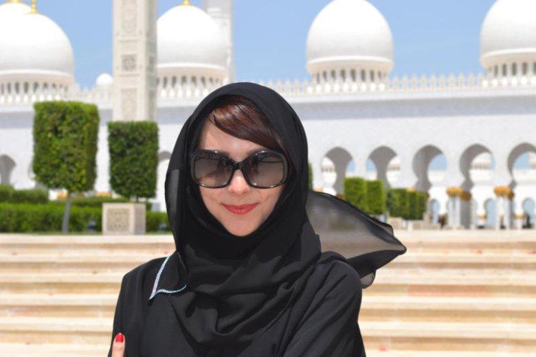 Autorka w hidżabie na tle meczetu.