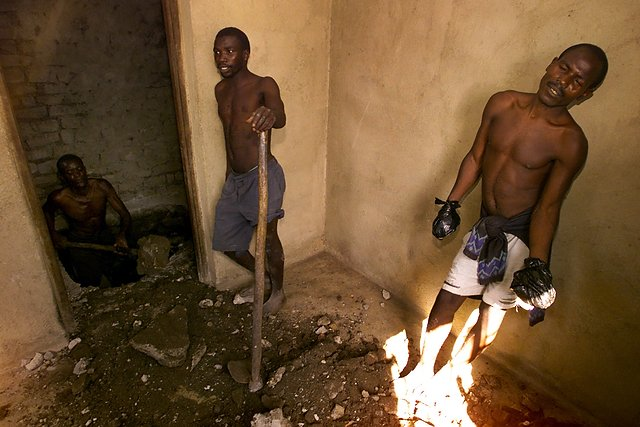 Wyczerpani więźniowie w chwili odpoczynku od pracy przy ekshumacji ciał ukrytych pod podłogą domu należącego do przywódcy sekty.
